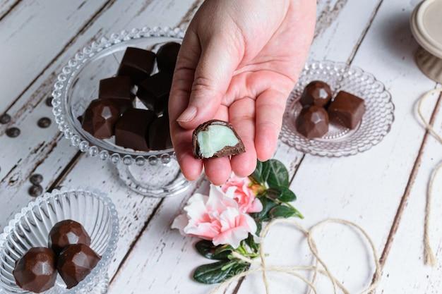 Dłoń trzymająca bonbon pogryziony na pół, z nadzieniem zielonym ganache. w tle czekoladki, sznurek i kwiaty.