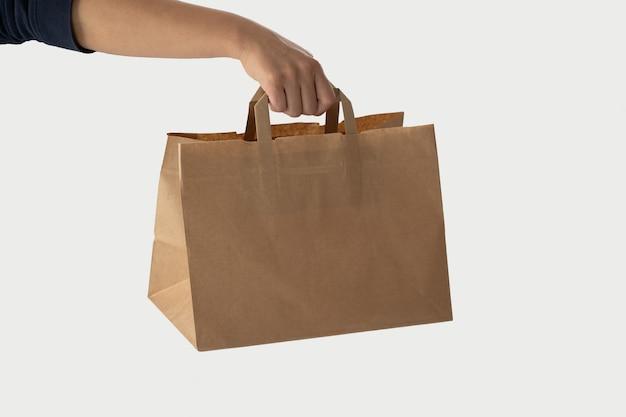 Dłoń trzymająca brązową papierową torbę na lunch na białym tle