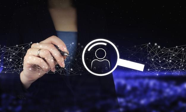 Dłoń trzymająca cyfrowy pióro graficzne i rysunek cyfrowy hologram człowieka, znak lidera na ciemnym tle niewyraźne miasta. koncepcja mediów społecznościowych. sieć komunikacji.