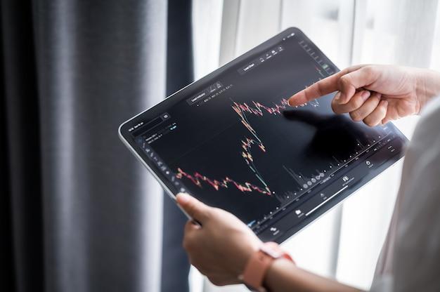 Dłoń trzymająca cyfrowy tablet wyświetla dane giełdowe z wykresem i wykresem do analizy i sprawdzenia przed obrotem akcjami online