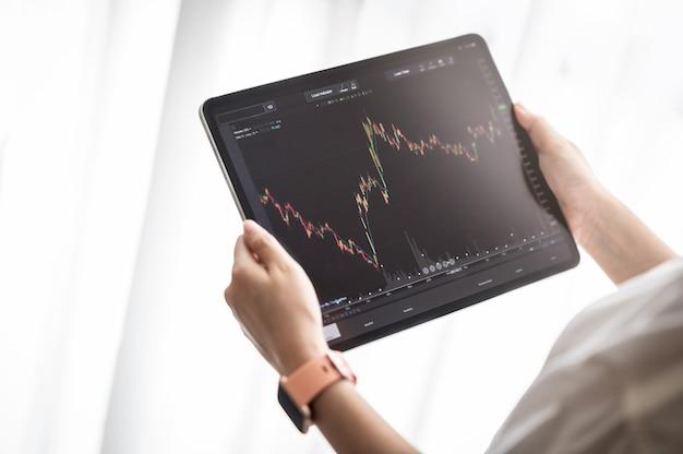 Dłoń trzymająca cyfrowy tablet wyświetla dane giełdowe z wykresem i wykresem do analizy