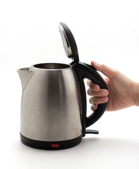 Dłoń trzymająca czajnik i otwórz pokrywę. srebrny czajnik elektryczny na białym tle, czajnik, szybkie ogrzewanie. nowoczesna technologia warzenia piwa.