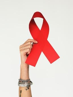 Dłoń trzymająca czerwony ribbin dla wsparcia pacjenta z rakiem