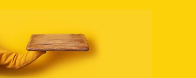 Dłoń trzymająca deskę na żółtym tle, widok perspektywiczny, obraz panoramiczny
