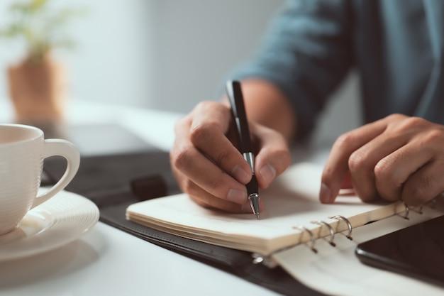 Dłoń trzymająca długopis i pisząca notatkę na stole lista kontrolna uwaga pamiętaj o koncepcji planowania