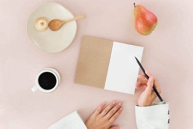 Dłoń trzymająca długopis pisząca notatkę