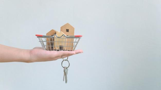 Dłoń trzymająca drewniany dom w koszu i pęku kluczy do domu