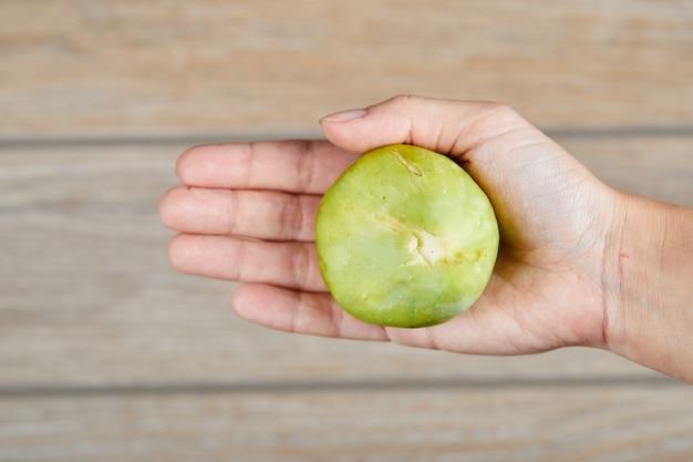 Dłoń trzymająca figę na drewnianym.