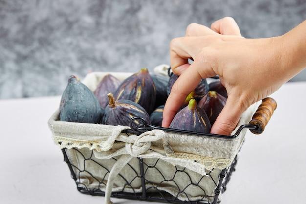 Dłoń trzymająca figę z kosza na białym i marmurze.