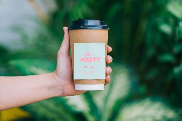 """Dłoń trzymająca filiżankę kawy ze słowem """"be happy"""""""