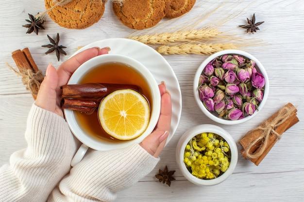 Dłoń trzymająca filiżankę z czarną herbatą z cynamonem