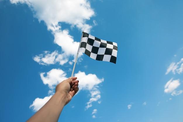 Dłoń trzymająca flagę z szachownicą