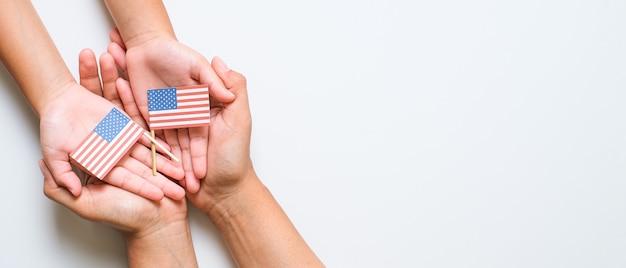 Dłoń trzymająca i dotykająca narodowa mini flaga amerykańska. koncepcja światowego dnia weterana