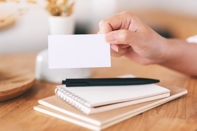 Dłoń trzymająca i pokazująca białą pustą wizytówkę