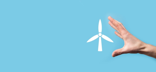 Dłoń trzymająca ikonę wiatraka, który wytwarza energię środowiskową na niebieskiej powierzchni