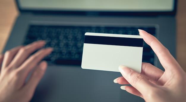 Dłoń trzymająca kartę kredytową i naciśnij laptop wpisz kod płatności za produkt.