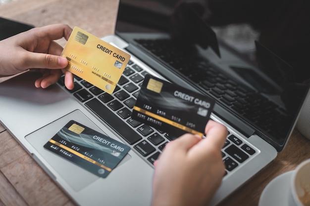 Dłoń trzymająca karty kredytowe dorywczo pracy przy użyciu komputera przenośnego z filiżanką kawy w kawiarni