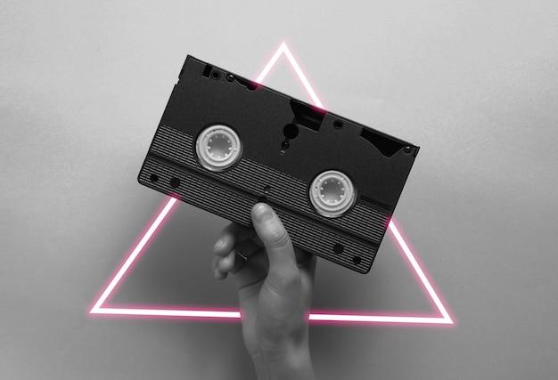 Dłoń trzymająca kasetę wideo.