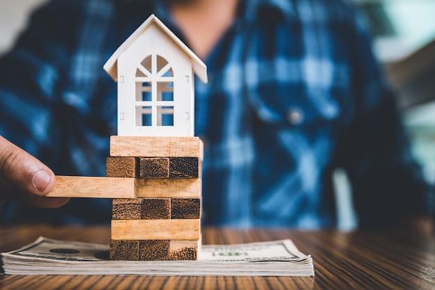 Dłoń trzymająca kawałek bloku drewna z białym modelem domu na banknot dolara.