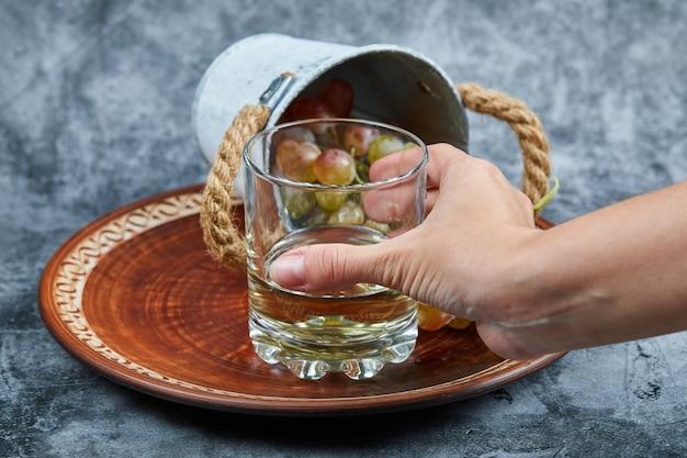 Dłoń trzymająca kieliszek białego wina i małe wiaderko winogron na marmurowej powierzchni.