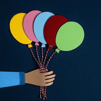 Dłoń trzymająca kilka kolorowych balonów papierowych. karta zaproszenie na przyjęcie balonów.