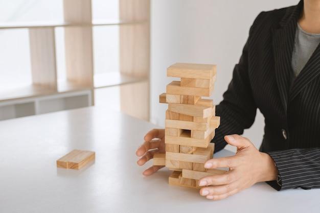 Dłoń trzymająca klocki gra w drewno koncepcja ryzyko zarządzania i strategii rozwoju planu biznesowego pracy zespołowej