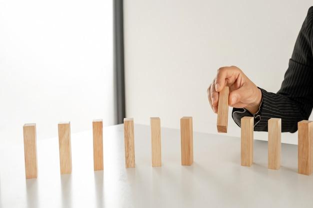 Dłoń trzymająca klockowa gra z drewna koncepcja ryzyko zarządzania i strategii rozwoju planu biznesowego pracy zespołowej