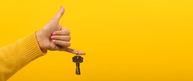 Dłoń trzymająca klucze od domu na żółtej przestrzeni
