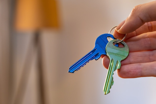 Dłoń trzymająca klucze z pokojem na tle wynajem sprzedam kup mieszkanie biznes nieruchomości