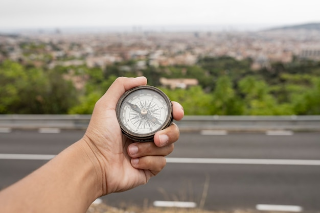 Dłoń trzymająca kompas, a w tle miasto