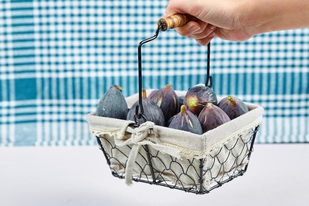 Dłoń trzymająca kosz fioletowych fig na białym tle z niebieskim obrusem.