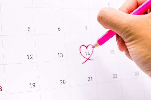 Dłoń trzymająca kredkę do pisania 14 lutego z różowym sercem w kalendarzu