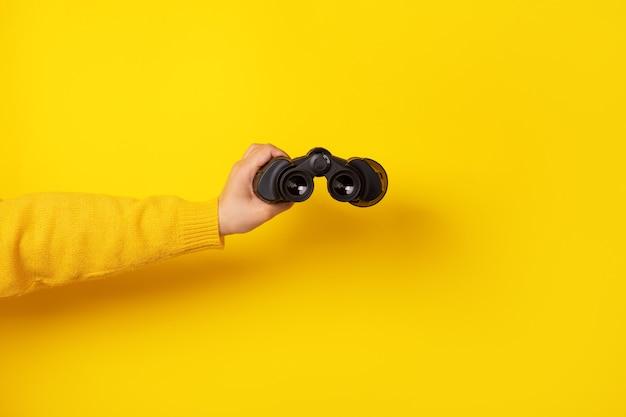 Dłoń trzymająca lornetkę na żółtym tle