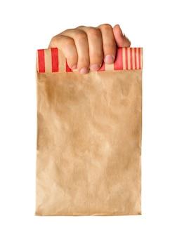 Dłoń trzymająca lub podająca brązową papierową torbę