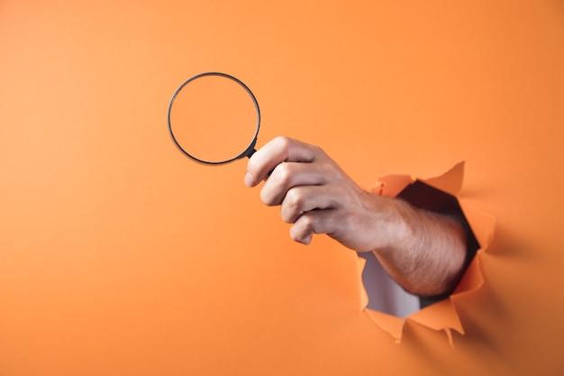 Dłoń trzymająca lupę na pomarańczowym tle