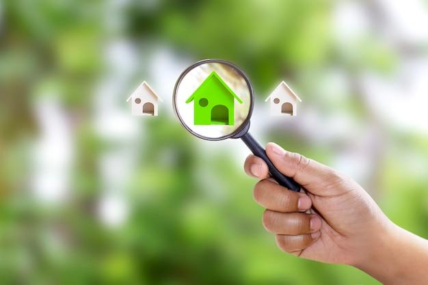 Dłoń trzymająca lupę wybierająca model zielonego domu na zielonym tle ekologiczna energooszczędna koncepcja domu