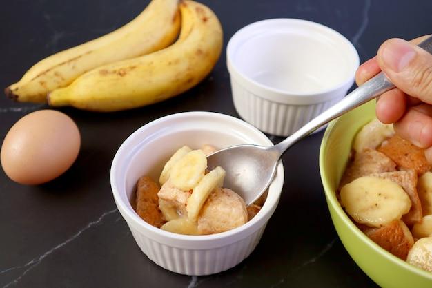 Dłoń trzymająca łyżkę wkładanie mieszanki do miski do pieczenia chleba bananowego budyń