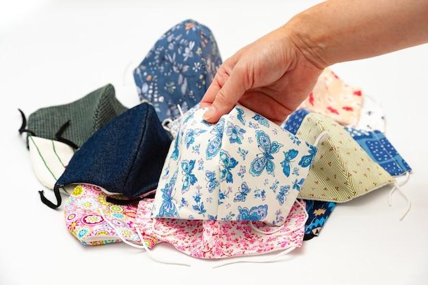 Dłoń trzymająca maski z tkaniny w kolorach niebieskim i białym