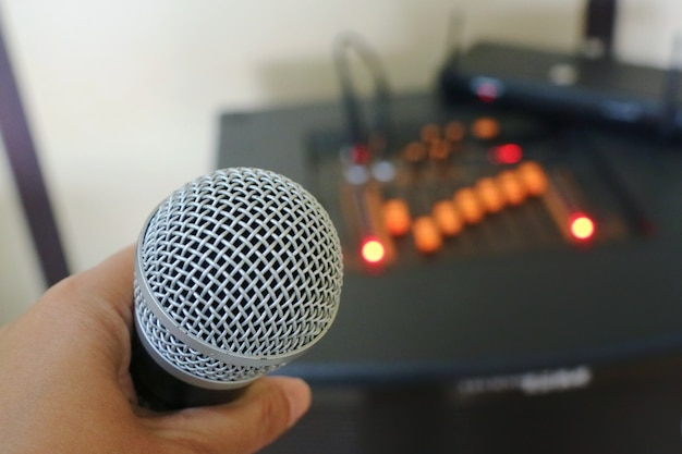 Dłoń trzymająca mikrofon z rozmytym analogowym mikserem dźwięku, radio kontrolera audio.