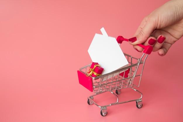Dłoń trzymająca miniaturowy koszyk na zakupy