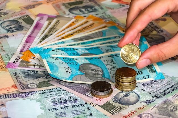 Dłoń trzymająca monetę 5 rupii powyżej 10 20 50 100 200 500 i 2000 rupii indyjskich