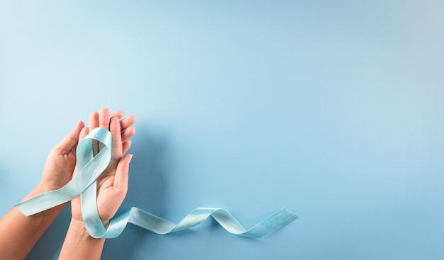 Dłoń trzymająca niebieską wstążkę, symboliczny kolor łuku podnosząca świadomość w dzień cukrzycy