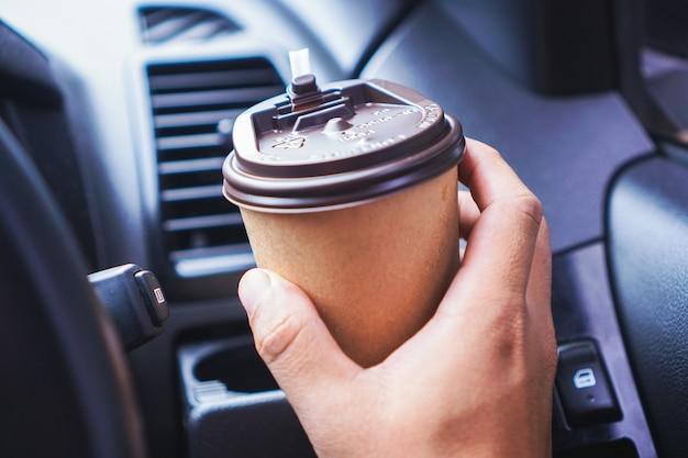 Dłoń trzymająca papierową filiżankę kawy podczas jazdy samochodem rano