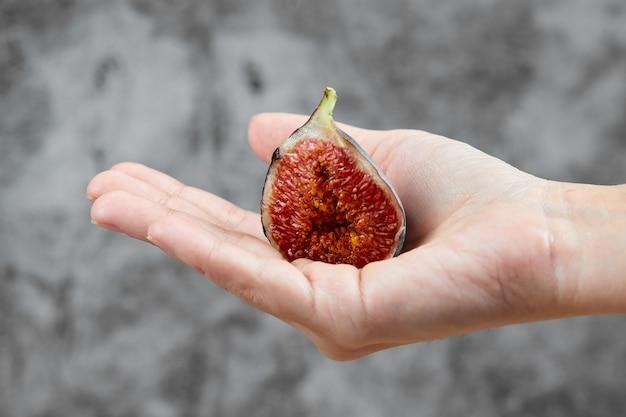 Dłoń trzymająca pół plasterka figi na marmurze.