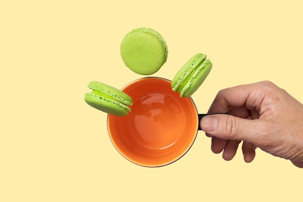Dłoń trzymająca pomarańczowy kubek z opadającymi kawałkami makaroników pistacjowych.