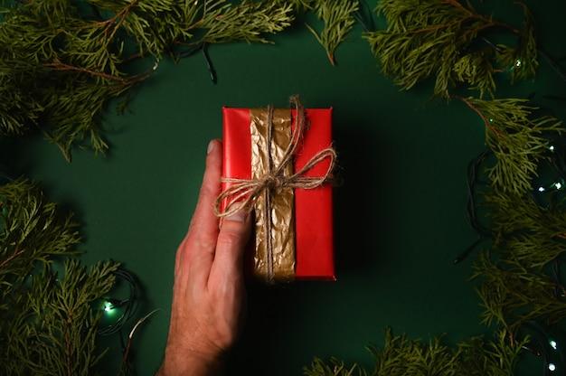 Dłoń trzymająca prezent na nowy rok na ciemnozielonym tle bożego narodzenia.
