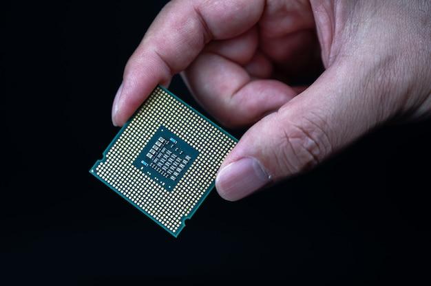 Dłoń trzymająca procesor na czarnym tle
