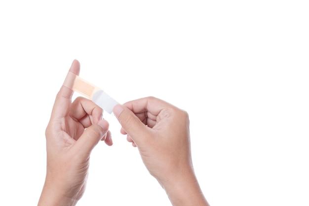 Dłoń trzymająca przylepny bandaż pierwszej pomocy, gips medyczny