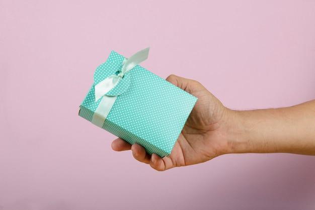 Dłoń trzymająca pudełko dostarczane do kogoś.