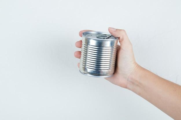 Dłoń trzymająca puszkę gotowanej słodkiej kukurydzy.